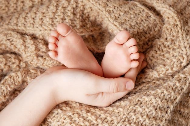 Stopy dziecka w rękach brata. małe stopy noworodka zbliżenie. szczęśliwa rodzina koncepcja.