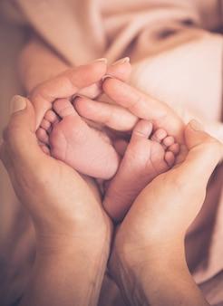 Stopy dziecka w rękach matki. małe stopy noworodka na kobiece dłonie w kształcie serca zbliżenie. mama i jej dziecko. szczęśliwa rodzina koncepcja. piękny koncepcyjny obraz macierzyństwa.