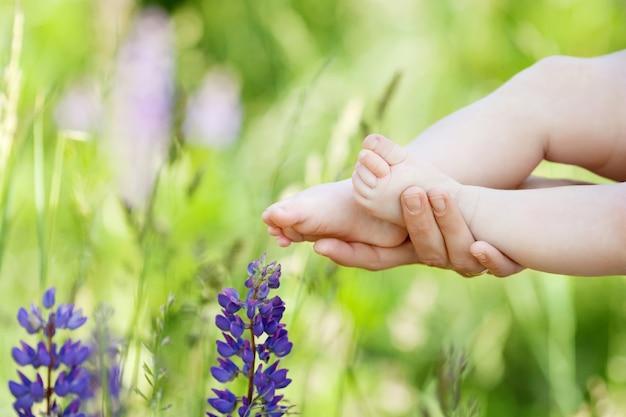 Stopy dziecka w rękach matki. małe stopy noworodka na kobiece dłonie w kształcie zbliżenie. mama i jej dziecko. szczęśliwa rodzina koncepcja. piękny koncepcyjny obraz macierzyństwa
