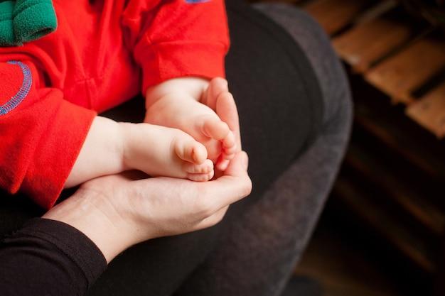Stopy dziecka w rękach matki