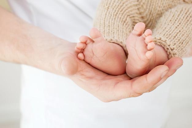 Stopy dziecka w rękach ojca. małe stopy noworodka na męskich rękach zbliżenie. tata i jego dziecko. szczęśliwa rodzina koncepcja.