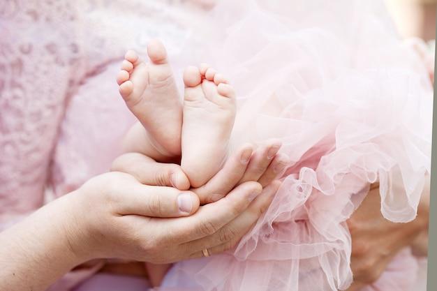 Stopy dziecka w rękach rodziców.