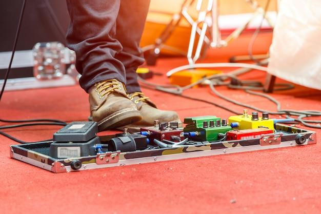 Stopy gitarzysty na scenie z zestawem pedałów efektu zniekształceń. selektywne skupienie