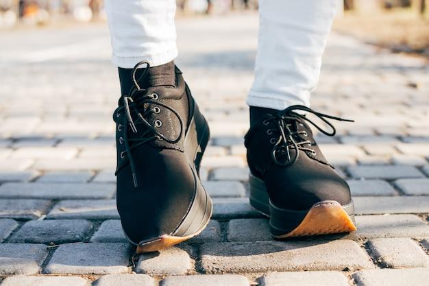 Stopy kobiet w czarne buty na chodniku w słoneczny dzień