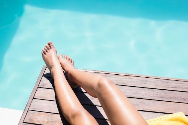 Stopy kobiety na krawędzi basenu w słoneczny dzień