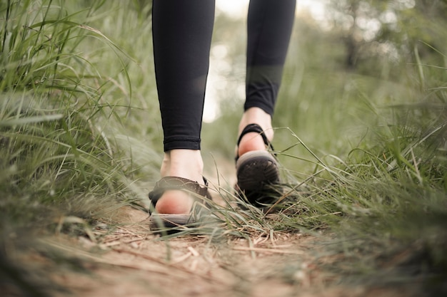 Stopy kobiety na trawiastej polnej drodze
