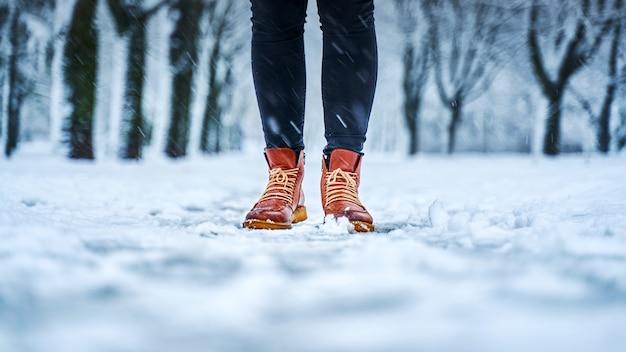 Stopy kobiety na zaśnieżonym chodniku w brązowych butach
