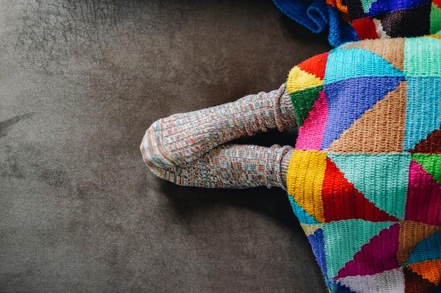 Stopy kobiety w skarpetkach na brązowej kanapie pokrytej patchworkowym kocem