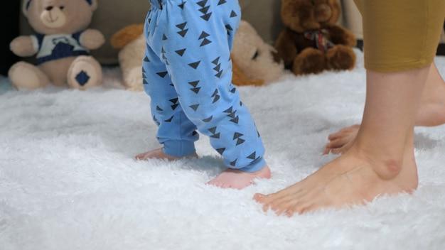 Stopy mamy i dziecka kroczące od prawej do lewej. koncepcja pierwszych kroków dziecka. zbliżenie