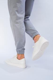 Stopy męskie w kolorze białym trampki codzienne wykonane ze skóry naturalnej na sznurowaniu. zdjęcie wysokiej jakości