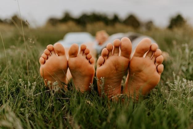 Stopy mężczyzny i kobiety stóp faceta i dziewczyny na trawie