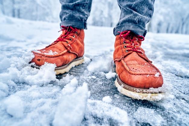 Stopy mężczyzny na zaśnieżonym chodniku w brązowych butach