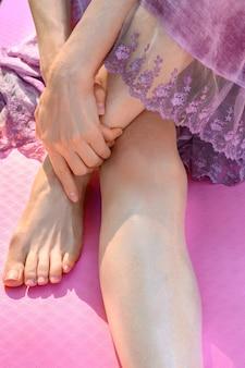 Stopy młodej kobiety ćwiczącej jogę na różowej macie fitness