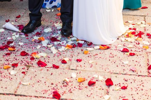 Stopy młodej pary w dniu ślubu z biało-czerwonymi płatkami róż na podłodze. brak twarzy