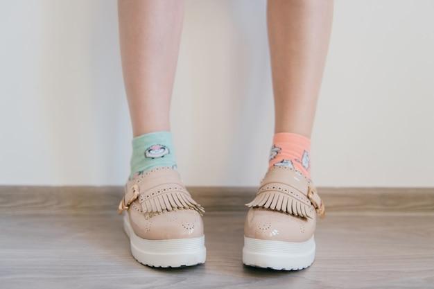 Stopy nagich kobiet w kobiecych biznesowych jasnych skórzanych butach z tankietką i białą podeszwą stojące w domu. kobiece stopy w niedopasowanych bawełnianych kolorowych skarpetach. niewinność i styl życia młodzieży.
