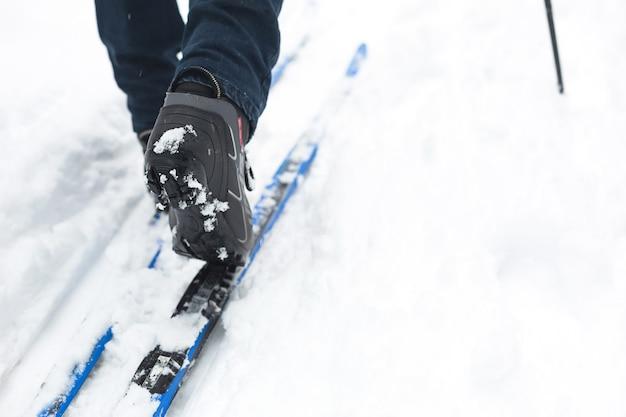 Stopy narciarza w butach narciarskich na nartach biegowych. chodzenie po śniegu, sporty zimowe, zdrowy tryb życia. close-up, copyspace