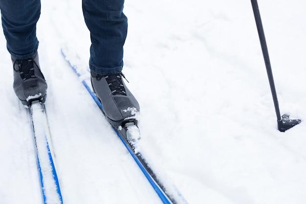 Stopy narciarza w butach narciarskich na nartach biegowych. spacery po śniegu, sporty zimowe, zdrowy tryb życia. zbliżenie, copyspace
