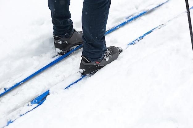 Stopy narciarza w butach narciarskich na nartach biegowych w śniegu