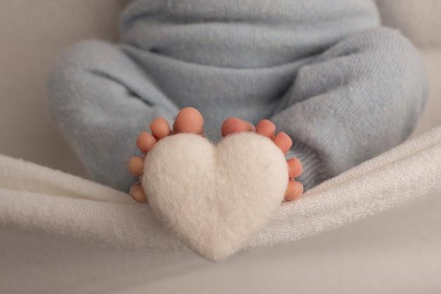 Stopy noworodka owinięte są w kocyk z dzianiny. palce noworodka trzymają białe, dziane serce. zdjęcie wysokiej jakości