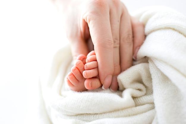 Stopy noworodka w rękach matki. matka trzyma w dłoniach stopy dziecka. szczęśliwa koncepcja rodziny. zdjęcie wysokiej jakości