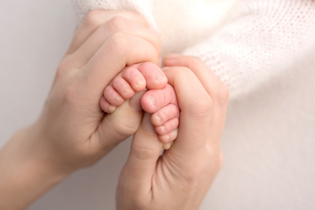 Stopy noworodka w rękach matki, rodzica. fotografia studyjna, białe tło. szczęśliwa koncepcja rodziny. zdjęcie wysokiej jakości