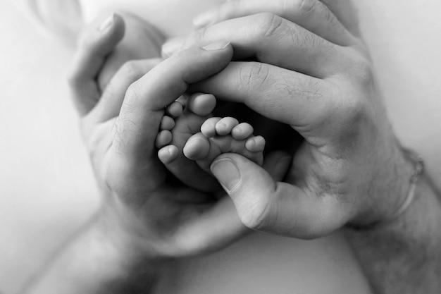 Stopy noworodka w rękach ojca, rodzica. fotografia czarno-biała. szczęśliwa koncepcja rodziny. zdjęcie wysokiej jakości