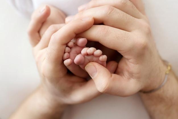 Stopy noworodka w rękach ojca, rodzica. fotografia studyjna, białe tło. szczęśliwa koncepcja rodziny. zdjęcie wysokiej jakości
