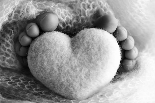 Stopy noworodka z drewnianym sercem, owinięte w miękki kocyk. czarno-biała fotografia studyjna. zdjęcie wysokiej jakości