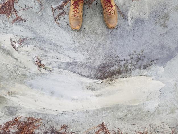 Stopy osoby w brązowych skórzanych butach stojących na wyblakłym betonowym podłożu