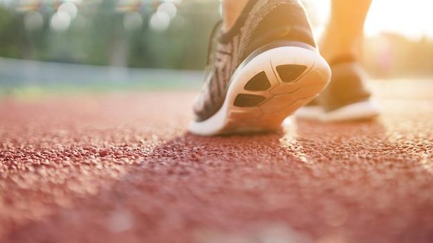 Stopy sportowca biegacza na bieżni. trening wellness.