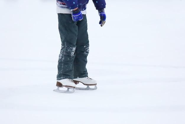 Stopy toczące się na łyżwach mężczyzna na lodowisku