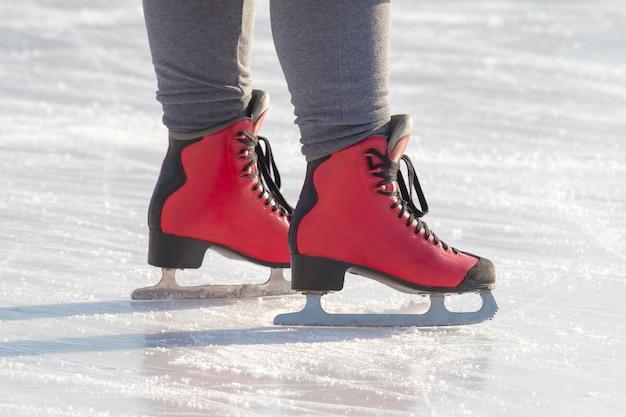 Stopy w czerwonych łyżwach na lodowisku. hobby i wypoczynek. sporty zimowe