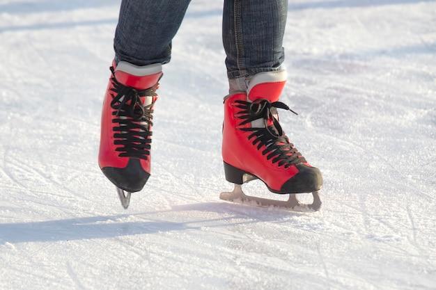 Stopy w czerwonych łyżwach na lodowisku.