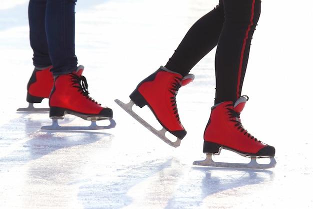 Stopy w czerwonych łyżwach na lodowisku