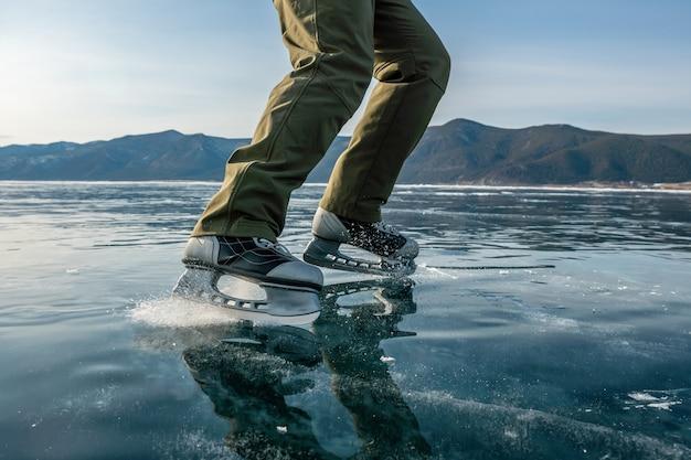 Stopy w łyżwach na pięknym niebieskim popękanym lodzie zamarzniętego jeziora