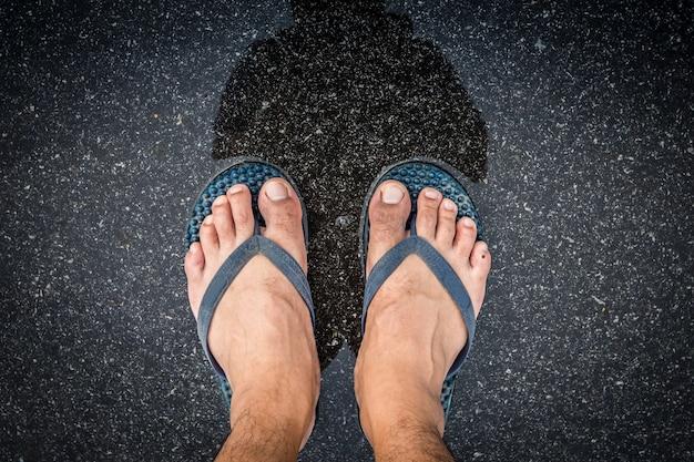 Stopy w sandałach azjatyckich mężczyzn nóg z mokrą ulicą