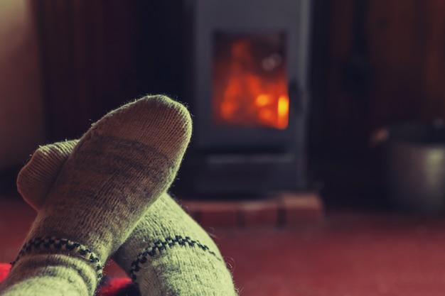 Stopy w skarpetach z wełny zimowej przy kominku