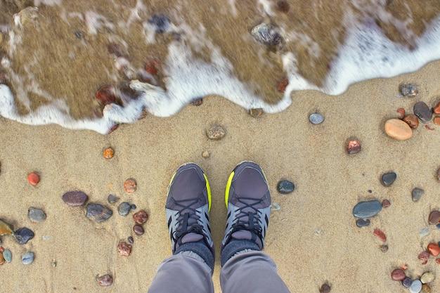 Stopy w trampkach na plaży. nadchodzi fala