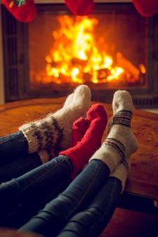 Stopy w wełnianych skarpetkach ogrzewają się przy płonącym kominku w domu