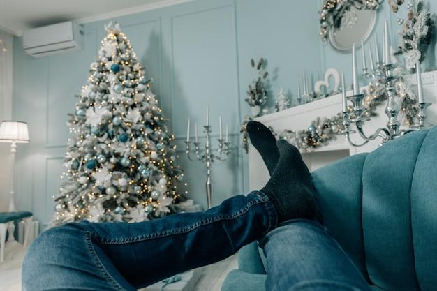 Stopy w wełnianych skarpetkach przy choince. człowiek relaksuje. zamknij się na nogach. zimowe i świąteczne wakacje koncepcji.