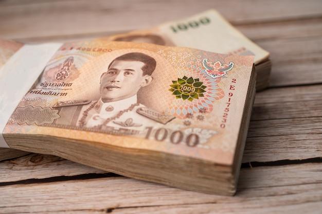 Stos banknotów bahtów tajskich na drewnianych.