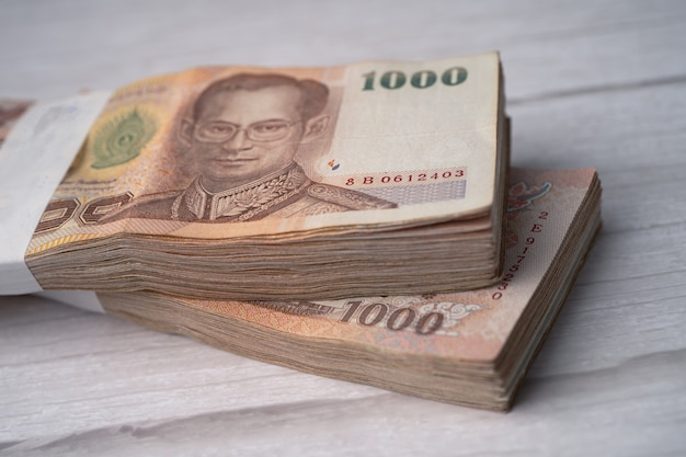 Stos banknotów bahtów tajskich na podłoże drewniane.