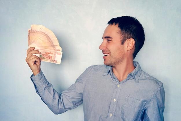 Stos banknotów pięć tysięcy rubli rosyjskich w ręce mężczyzny na niebieskim tle. pakiet banknotów 5000 rubli federacji rosyjskiej.