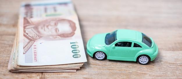 Stos banknotów tajlandzkich bahtów z samochodem.