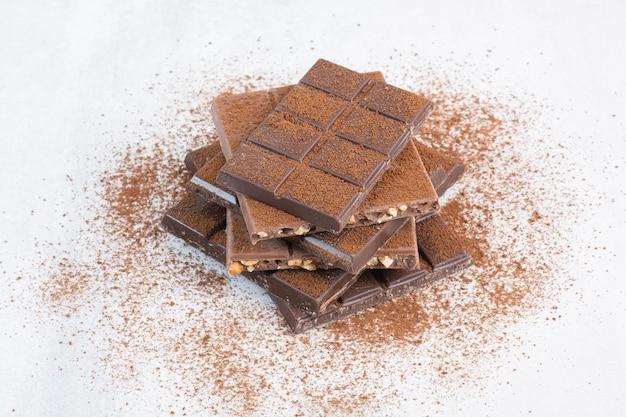 Stos batonów czekoladowych ozdobiony proszkiem kakaowym