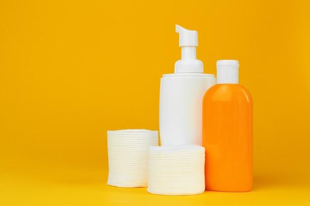 Stos bawełnianych krążków i butelka kosmetyczna skicare