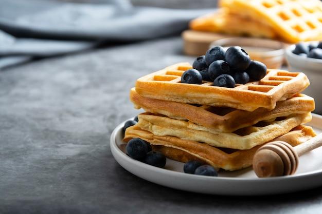 Stos belgijskich gofrów z jagodami i miodem na śniadanie. pyszne domowe ciasto. skopiuj miejsce