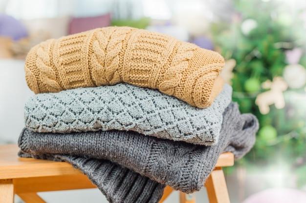 Stos białe przytulne swetry z dzianiny na drewnianym stole