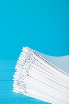 Stos białego papieru z klipsami na niebieskim tle.