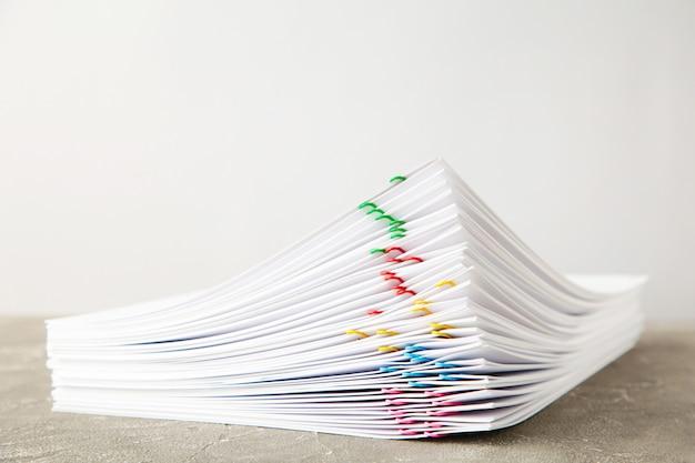 Stos białego papieru z klipsami na szarym tle